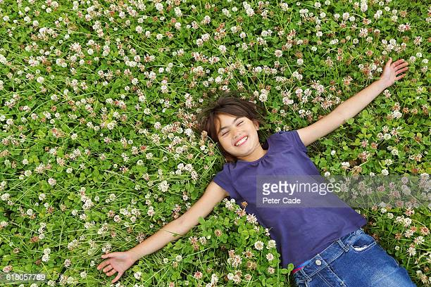 Young girl laying on back in grass and flowers