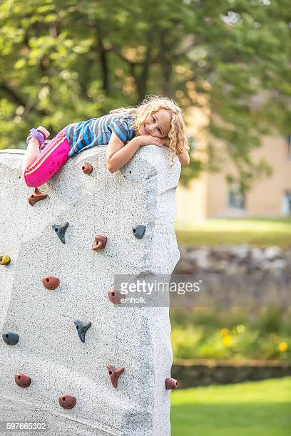 Young Girl Laying on Top of Rock Climbing Wall