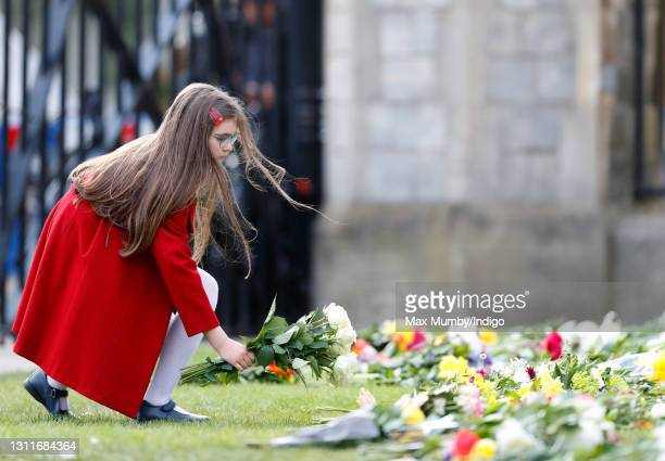Young girl lays a floral tribute outside the gates of Windsor Castle on April 9, 2021 in Windsor, England. The Queen has announced the death of her...
