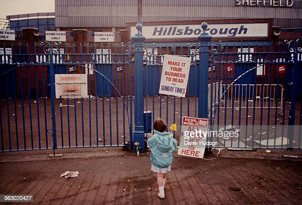 Young girl lays a single flower outside the entrance to Hillsborough Stadium after the stampede which resulted in the deaths of 96 people, Sheffield,...