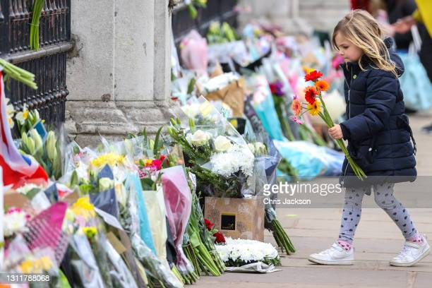 Young girl lays flowers as tribute to Prince Philip, Duke Of Edinburgh who died at age 99 outside Buckingham Palace on April 10, 2021 in London,...