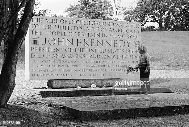 Young girl lays flowers at the John F Kennedy Memorial after the assassination of Senator Robert Kennedy, Runnymede, Surrey, England, 6th June 1968.