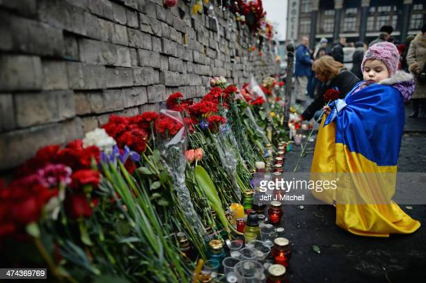 A young girl lays flowers left for antigovernment demonstrators killed in clashes with police on February 22 2014 in Kiev UkrainePrime Minister...