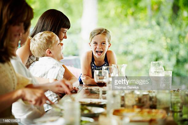 Young girl leaning on end of table laughing