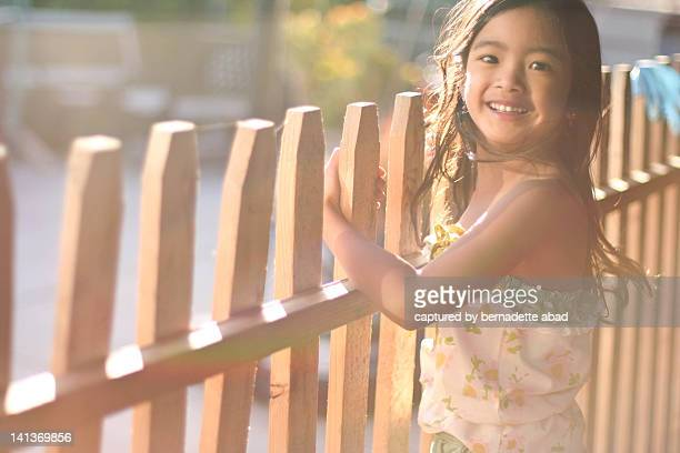 Young girl leaning on wood fence