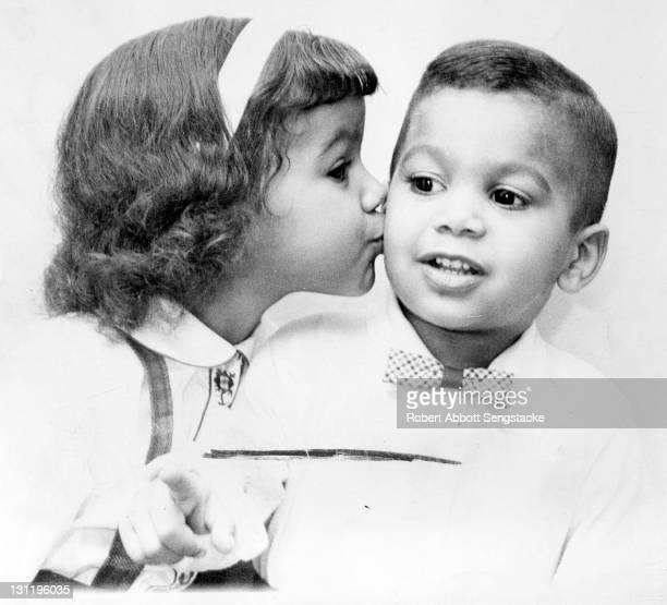 A young girl leans in to kiss a boy in a bow tie on his cheek 1960s