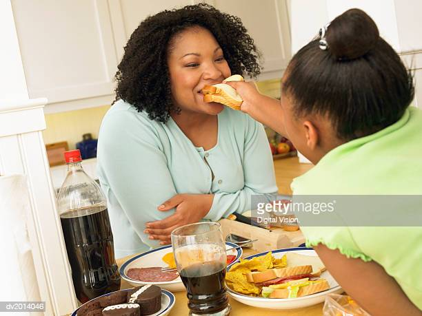 Young Girl Leans Over a Kitchen Table to Feed a Sandwich to Her Mum