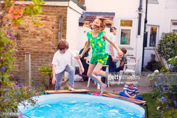 young girl leaping into a paddling pool - playing stock pictures, royalty-free photos & images