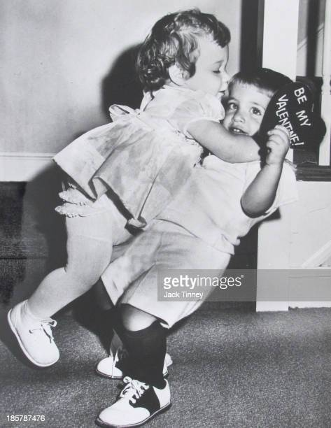 A young girl leaps onto a young boy the latter of whom holds a 'Be My Valentine' card 1960s