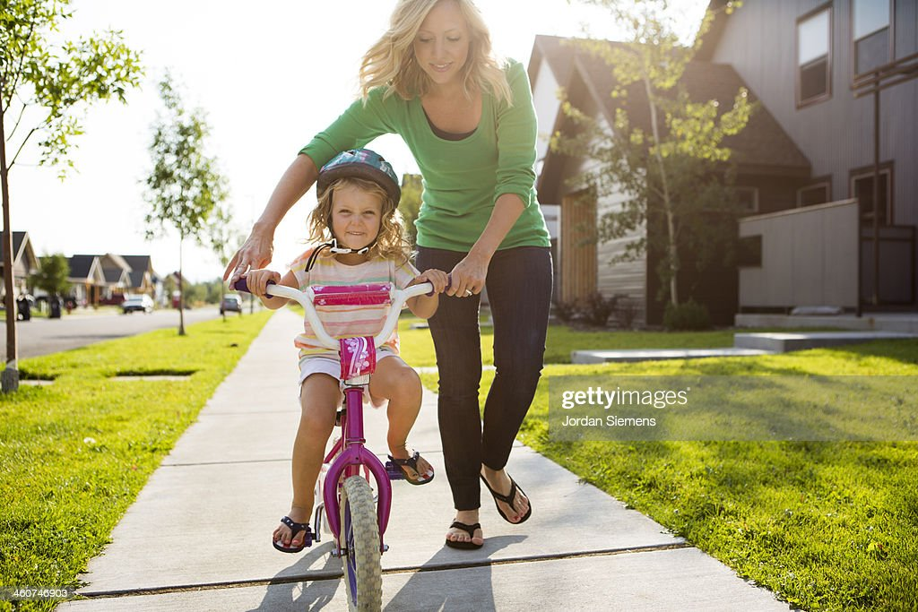 Young girl learning to ride a bike. : Stock Photo