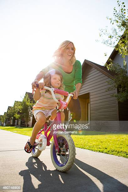 Young girl learning to ride a bike.