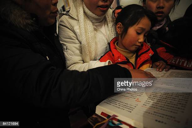 A young girl learns to read the Bible during a Christmas Eve mass at the temporary Bailu Township Church on December 24 2008 in Pengzhou of Sichuan...