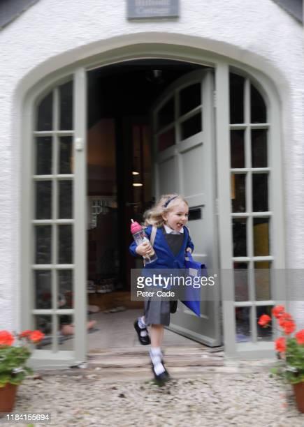 young girl leaving house to go to school - écolière photos et images de collection