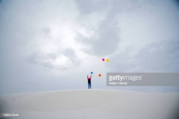 a young girl letting balloons go on a sand-dune. - roswell stock pictures, royalty-free photos & images