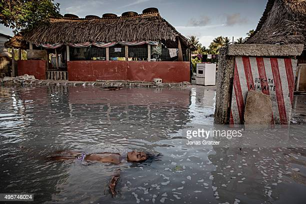 A young girl lies on her back in seawater that has flooded the village street in Eita The people of Kiribati are under pressure to relocate due to...