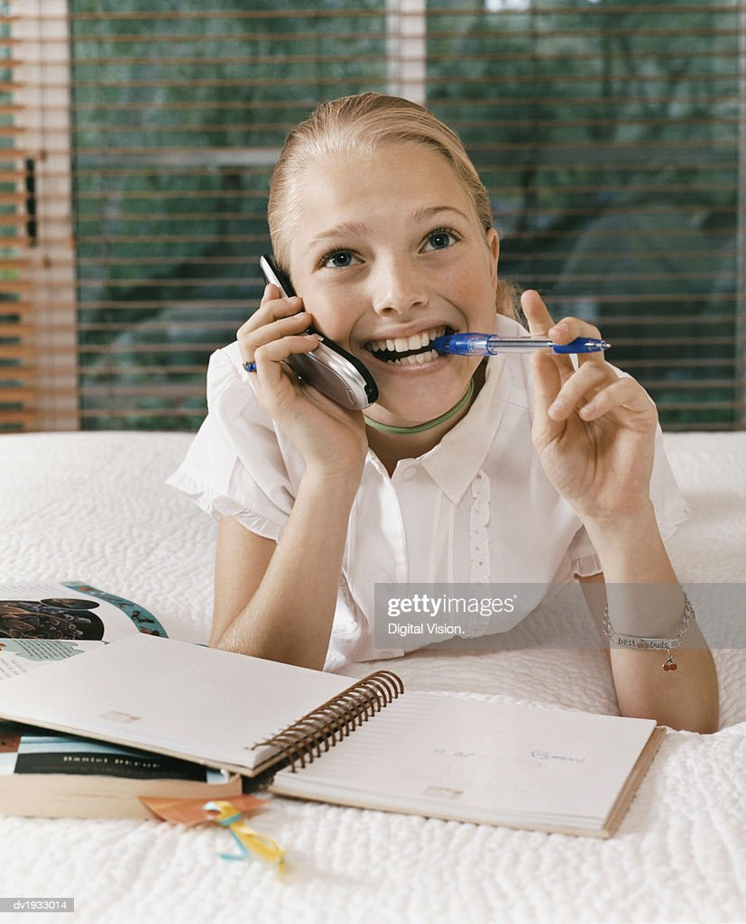 Young Girl Lies on Her Bed With a Diary, Chewing a Pen and Talking on Her Mobile Phone : Stock Photo