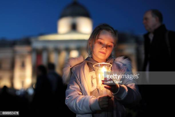 A young girl lights a candle during a candlelit vigil at Trafalgar Square on March 23 2017 in London England Four People were killed in Westminster...