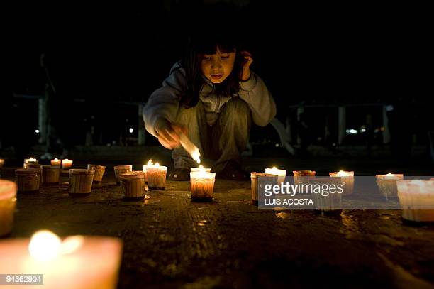 A young girl lights candles during a demonstration against Climate Chage in Mexico City on December 12 2009 In the framework of worldwide protests...