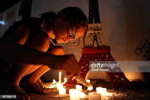 A young girl lights candles to honour victims of the Paris terror attacks at Alliance Francais Manila on November 16 2015 in Manila Philippines 129...