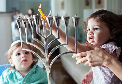 Young girl lights the Hanukkah menorah with help from adult 187288671