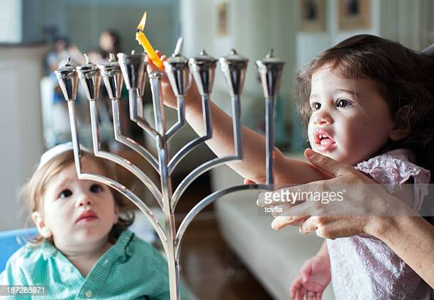 young girl lights the hanukkah menorah with help from adult - judaism stock pictures, royalty-free photos & images