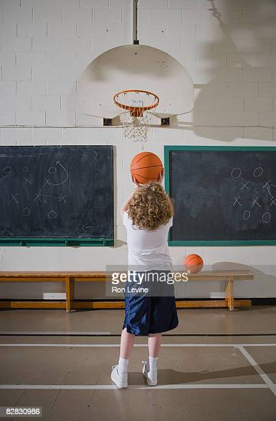 young girl lining up a basketball shot