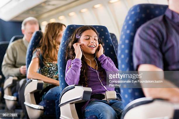 young girl listening to headphones on an airplane