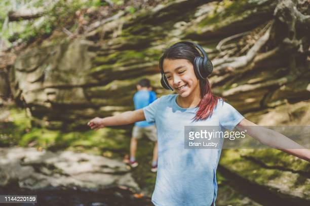 young girl listening to headphones outdoors - arlington virginia stock pictures, royalty-free photos & images