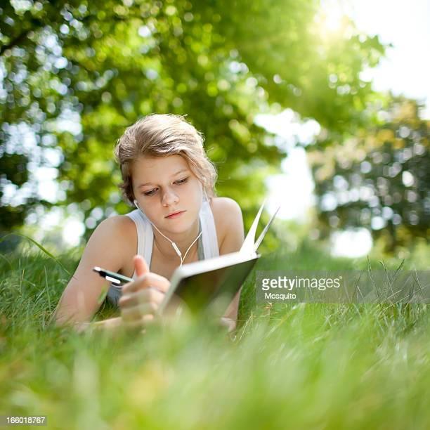 Beatiful adolescente estudiando en el parque