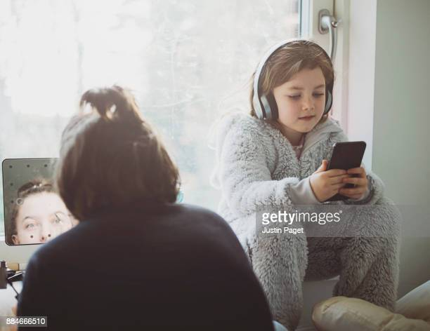 Young girl listening to music in sister's bedroom
