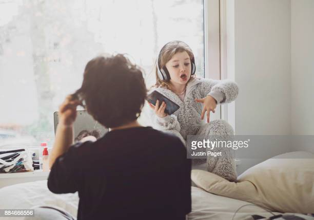 young girl listening to music in sister's bedroom - 18 19 jahre stock-fotos und bilder