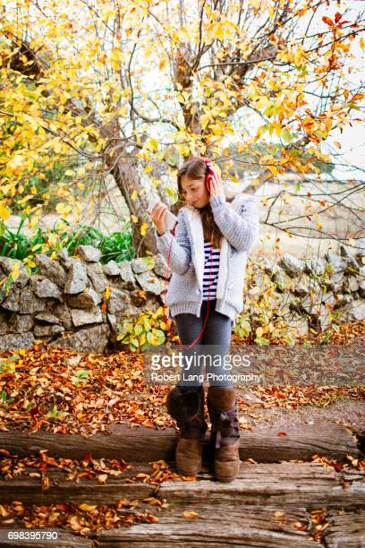 Young girl listening to music through headphones while outside under a colourful pretty tree during the fall