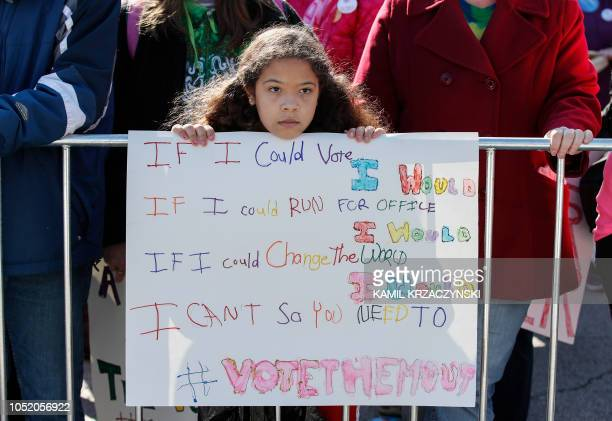 Young girl listens as women gather for a rally and march at Grant Park on October 13, 2018 in Chicago, Illinois to inspire voter turnout ahead of...
