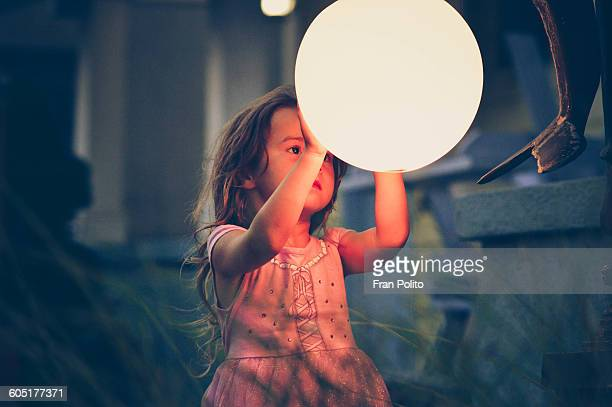 A young girl looking at a light at night.