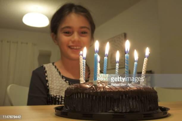young girl looking at birthday part cake - rafael ben ari foto e immagini stock