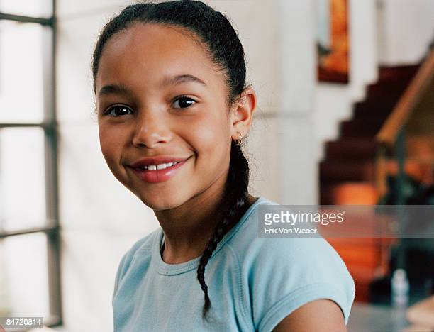 young girl looking at camera and smiling indoors - 8 9 jahre stock-fotos und bilder
