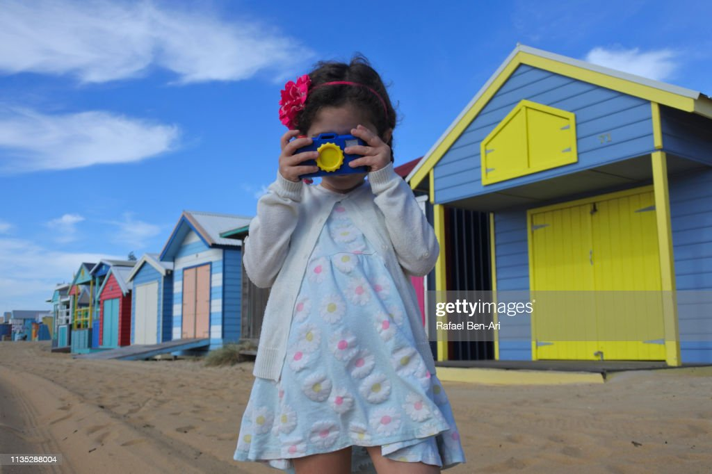 Young girl looking at camera photographing the Iconic Bathing Boxes of the Mornington Peninsula Victoria Australia. : Stock Photo