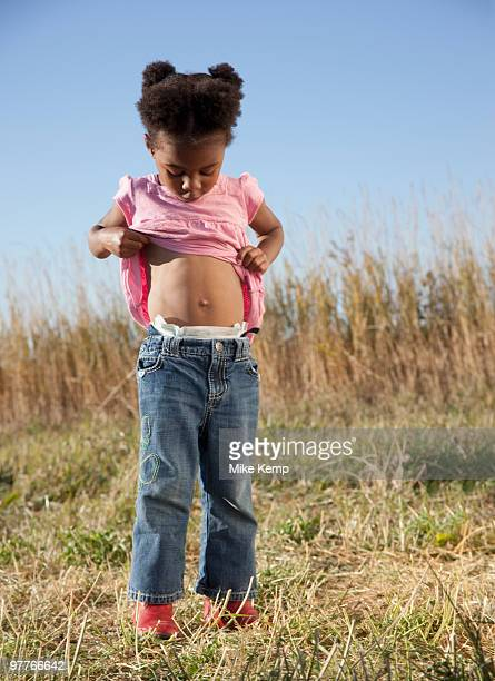 young girl looking at her belly button - belly button stock pictures, royalty-free photos & images