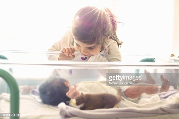Young girl looking at newborn baby brother