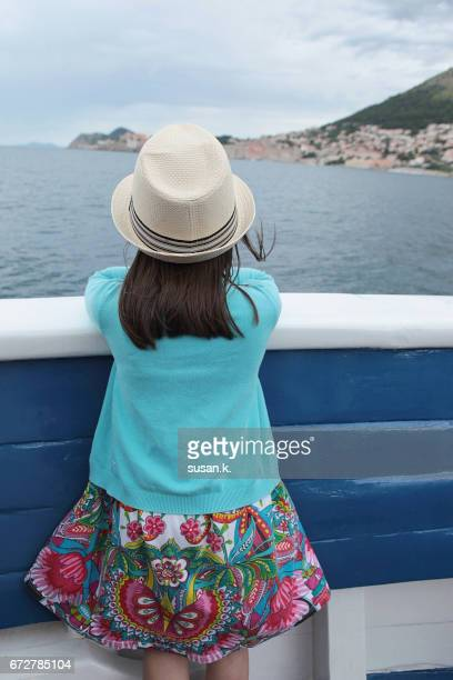 Young girl looking at old town from sailboat.