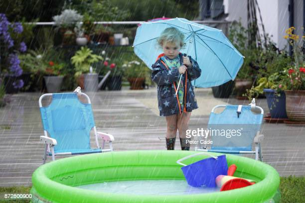 Young girl looking at paddling pool outside in the rain