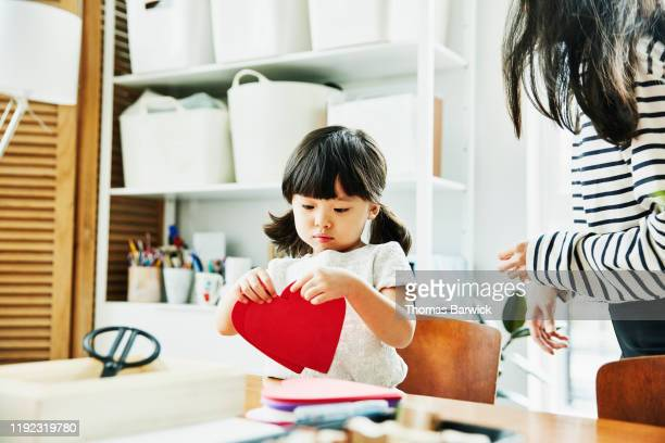 young girl looking at paper hearts while making valentines day cards in home - craft stock pictures, royalty-free photos & images