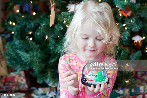 Young girl looking at snow globe figurine.