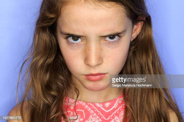young girl looking at the camera angry - misnoegd stockfoto's en -beelden