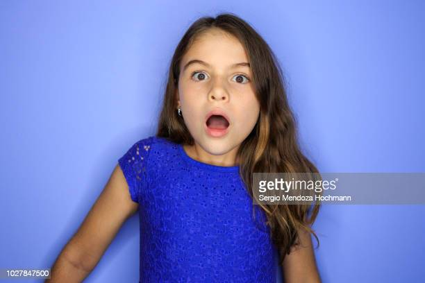 young girl looking at the camera surprised - surprise face kid - fotografias e filmes do acervo