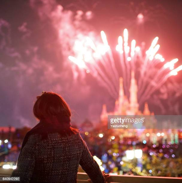 Young girl looking at the firework in holiday