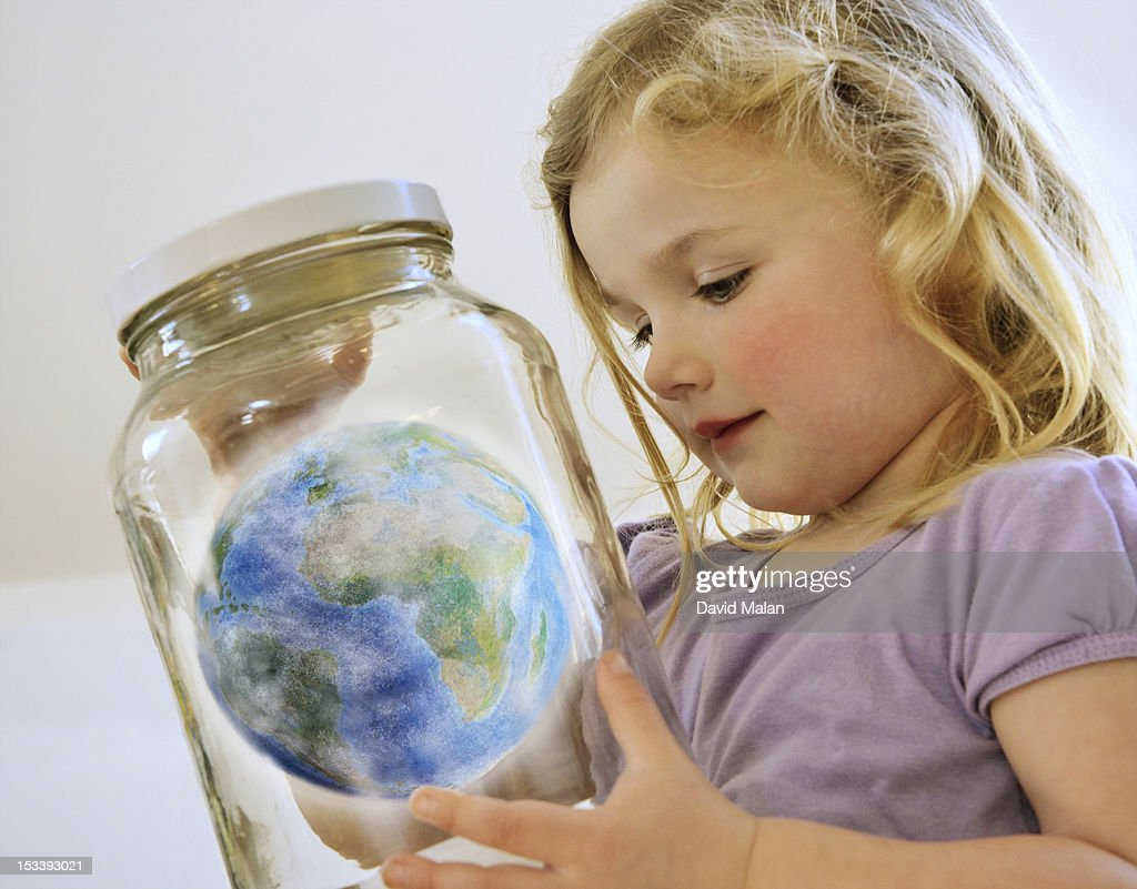 young girl looking at the world in a jar. : Stock Photo