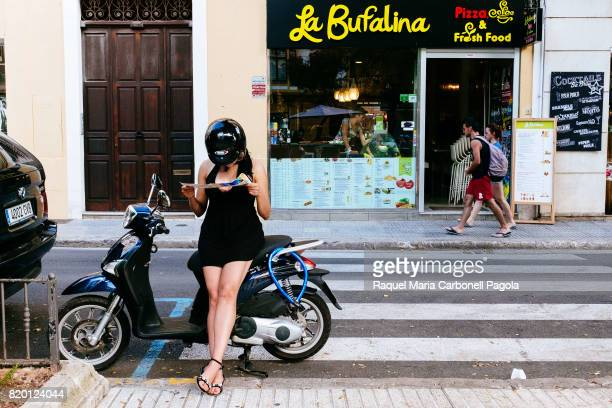 Young girl looking at tourist map and sitting on a motorbike in front of an italian restaurant in Vara de Rey promenade