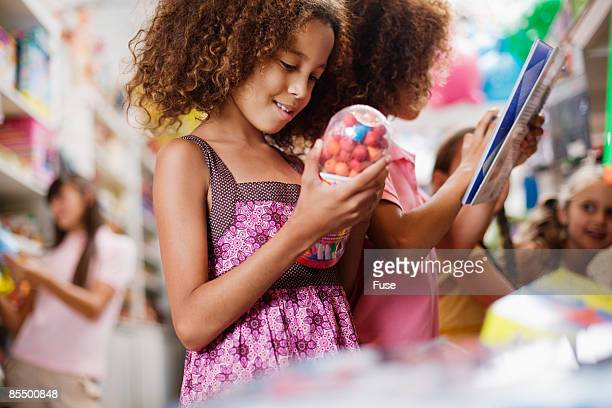 Young Girl Looking at Toy Gumball Machine