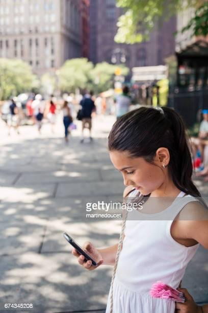 Ung flicka tittar ner en mobiltelefon i New York street.